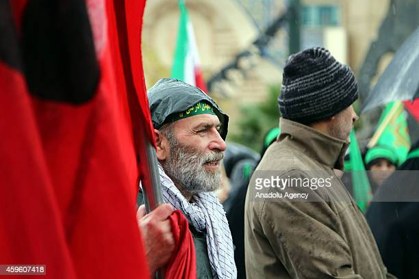 Iranian man holds flag during the celebrations marking the 35th anniversary of the Basij , a paramilitary volunteer militia established in 1979 by...