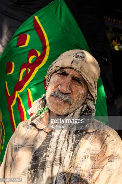 Iranian man rests after a mud bath on the day of Ashura the climax day of the Mourning of Muharram religious holiday in Khorramabad Iran on September...