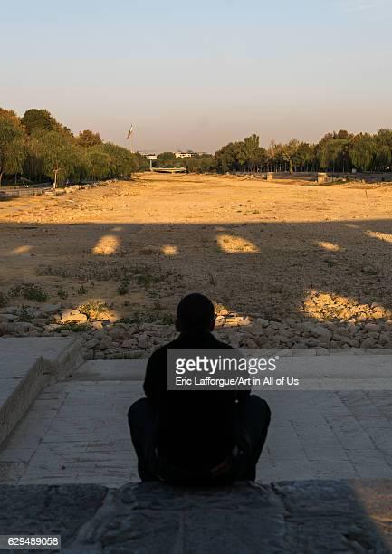 Iranian man sit on Khaju bridge Pol-e Khaju looking the dry Zayandeh river, Isfahan Province, Isfahan, Iran on October 13, 2016 in Isfahan, Iran.