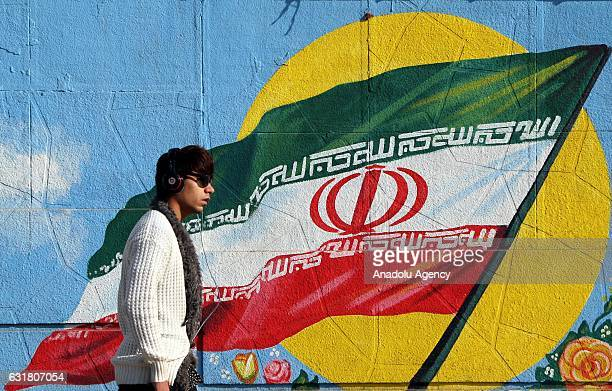 Iranian man walks past a wall painting in the shape of Iranian flag in Tehran Iran on the first anniversary of nuclear deal between Iran and world...