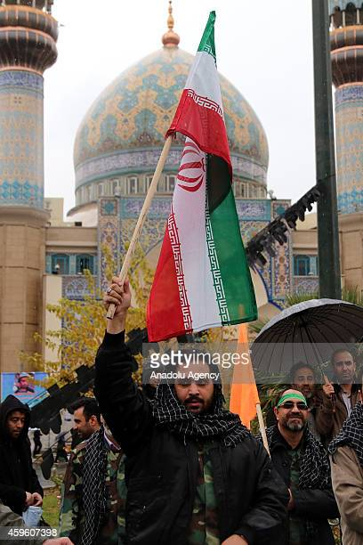 Iranian man waves Iranian flag during the celebrations marking the 35th anniversary of the Basij , a paramilitary volunteer militia established in...