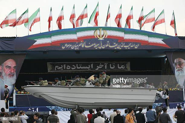 Iranian marines sit in a military speed boat passing by portraits of Iran's late founder of Islamic Republic Ayatollah Khomeini and Iran's supreme...
