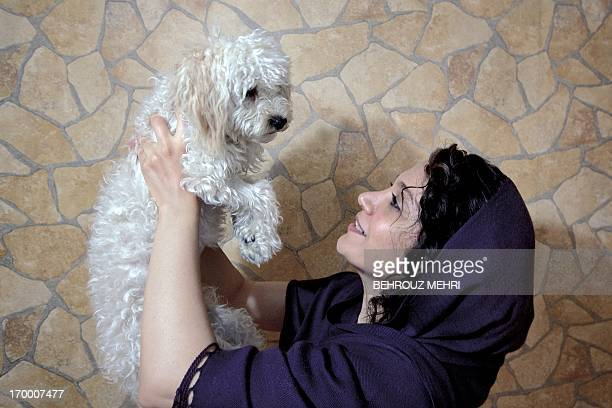 Iranian mechanic engineer Azar poses for a picture with her Terrier dog Pony in her bedroom in Tehran on May 28 2013 For decades pet dogs were rare...