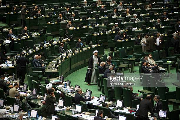 Iranian Members of Parliament attend a parliament session to discuss the annual budget bill which is being presented by the government in Tehran on...