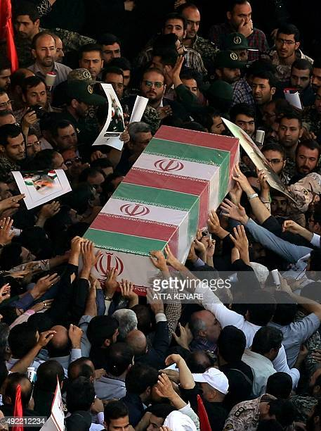 Iranian men carry the casket of Iran's Revolutionary Guards Brigadier General Hossein Hamedani during his funeral in Tehran on October 11 2015...