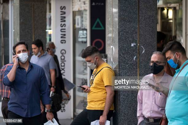 Iranian men check their smartphones as they stand in front of a shopping mall in northern Tehran on June 19, 2021. - Ultraconservative cleric Ebrahim...