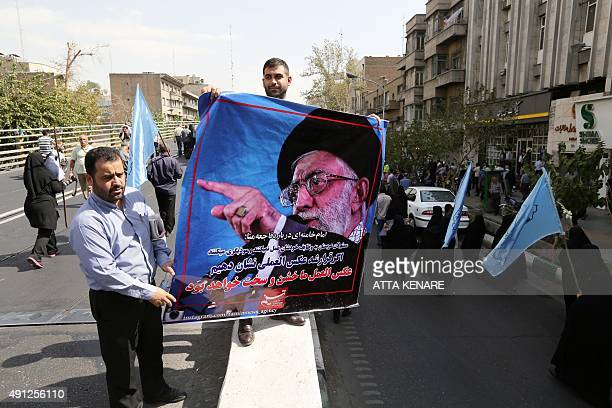 Iranian men hold a poster showing Iran's Supreme Leader Ayatollah Ali Khamenei during a funeral procession for some of the Iranian pilgrims who were...