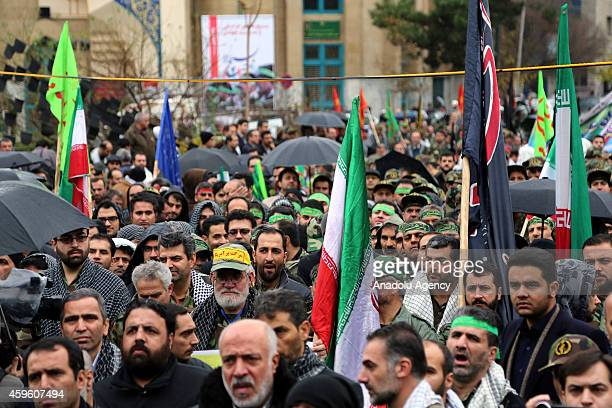 Iranian men hold flags during the celebrations marking the 35th anniversary of the Basij , a paramilitary volunteer militia established in 1979 by...