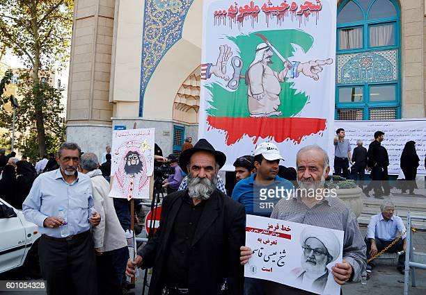 Iranian men holding a picture Bahraini Shiite cleric Sheikh Isa Qassim and a caricature of the Saudi king, participate in an anti-Saudi demonstration...
