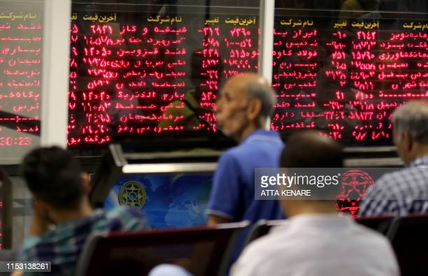 Iranian men monitor the stock market at Tehran Stock Exchange on July 1 2019 Iran's stock market is thriving despite US sanctions which have battered...