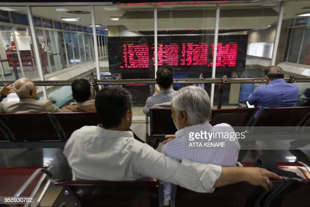 Iranian men monitor the stock market at the stock exchange in the capital Tehran on May 8 2018 Renewed nuclear sanctions would certainly cause severe...