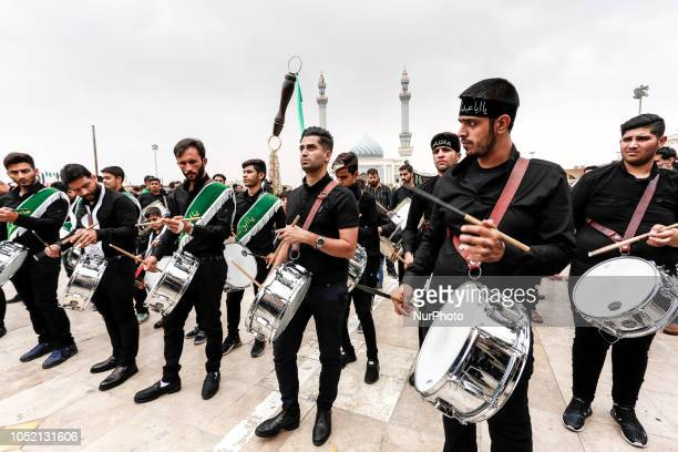 Iranian men play heartbeatlike traditional rhythm during a procession during the Mourning of Muharram religious holiday in Qom Iran on September 19...