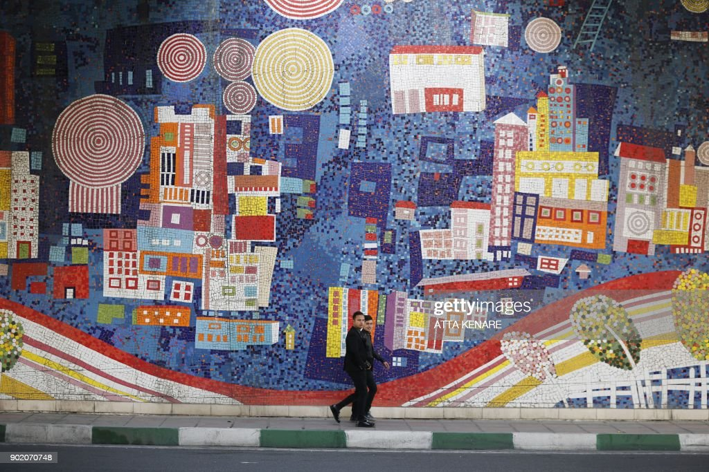 TOPSHOT - Iranian men walk past a mosaic decorated wall in downtown ...