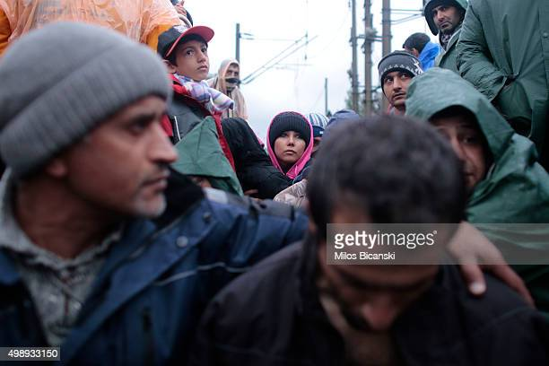 Iranian migrants some of whom are on hunger strike with their mouths sewed shut stand on rail tracks at the border between Greece and Macedonia...