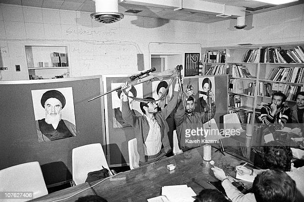 Iranian militant Islamist student leader Ebrahim Asgharzadeh and a fellow student display arms to the members of international press captured inside...