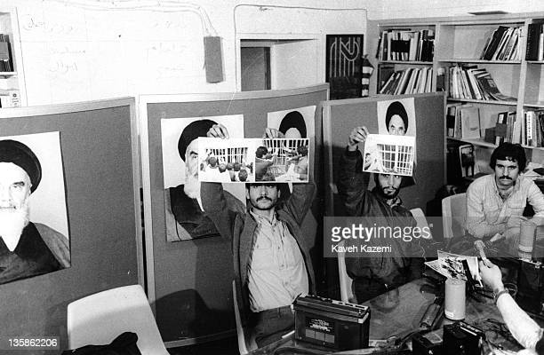 Iranian militant Islamist student leader Ebrahim Asgharzadeh and a fellow student display photos taken during the occupation to the members of...