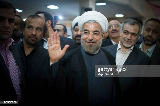 Iranian moderate presidential candidate Hassan Rowhani waves as he leaves a polling station after voting in the first round of the presidential...