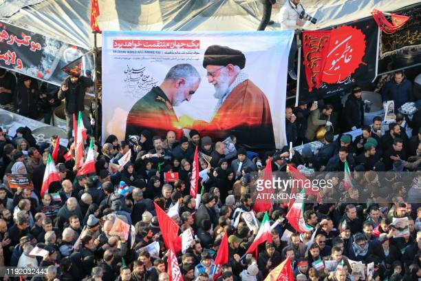Iranian mourners carry a picture of Iran's Supreme Leader Ayatollah Ali Khamenei granting the Order of Zolfaghar the highest military honour of Iran...