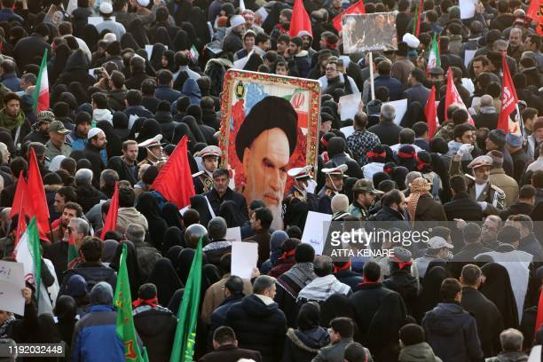 Iranian mourners carry a picture of the late founder of the Islamic republic Ayatollah Ruhollah Khomeini during a funeral procession in the capital...