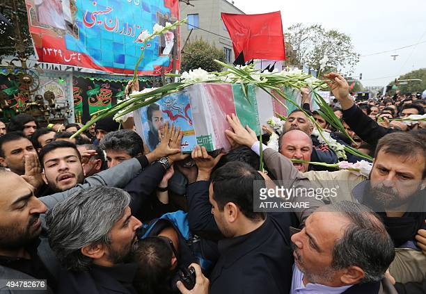 Iranian mourners carry the casket of Islamic Republic's Revolutionary Guards Corps' member Abdollah Bagheri who was killed fighting in Syria during...