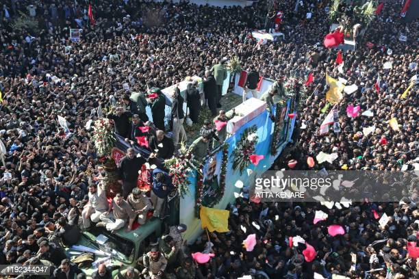 Iranian mourners gather around a vehicle carrying the coffin of slain top general Qasem Soleimani during the final stage of funeral processions in...