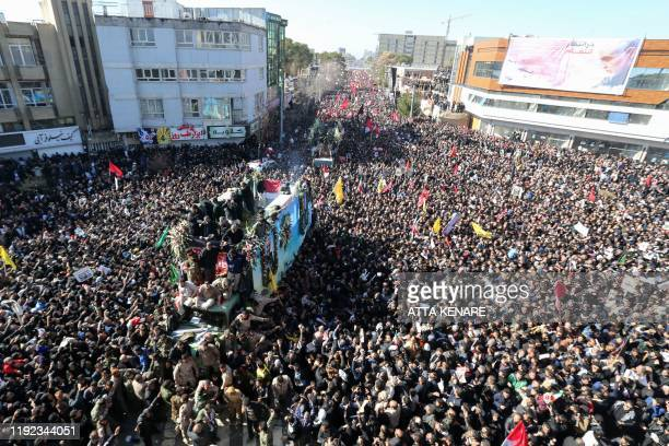 Iranian mourners gather around a vehicle carrying the coffin of slain top general Qasem Soleimani during the final stage of funeral processions, in...