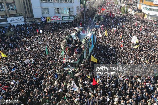 TOPSHOT Iranian mourners gather around a vehicle carrying the coffin of slain top general Qasem Soleimani during the final stage of funeral...