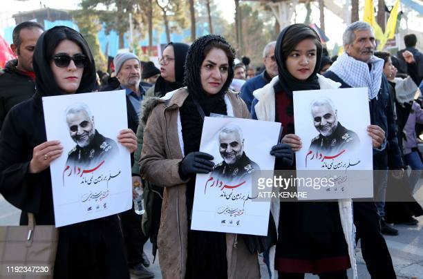 Iranian mourners hold posters of slain top general Qasem Soleimani during the final stage of funeral processions in his hometown Kerman on January 7...