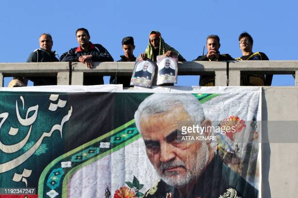Iranian mourners stand on a bridge during the final stage of funeral processions for slain top general Qasem Soleimani in his hometown Kerman on...