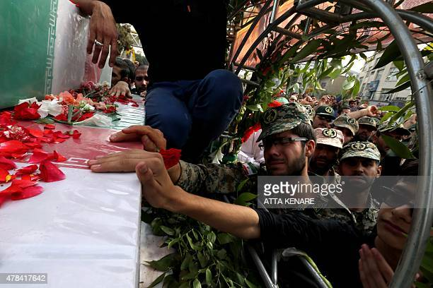 Iranian mourners touch the coffins of Mohammad Hamidi Hasan Ghafari and Ali Amrai members of the Islamic Republic's Revolutionary Guards reportedly...