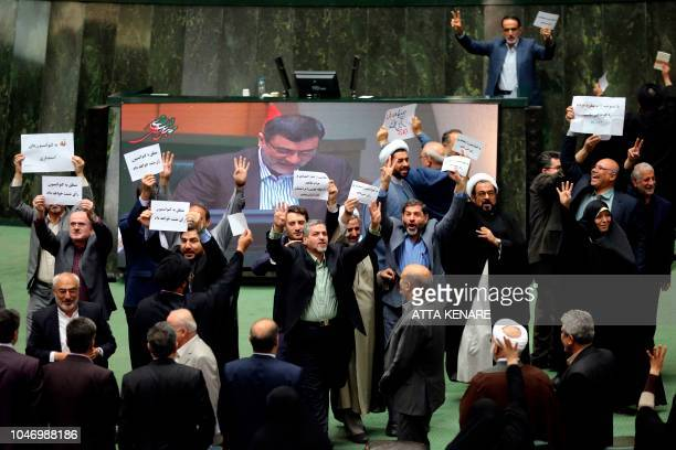 Iranian MP's display their disagreement over the a bill to counter terrorist financing in parliament in Tehran on October 7, 2018. - The bill, one of...