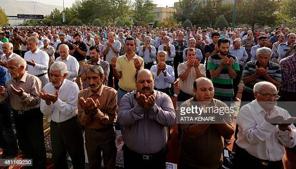 Iranian Muslim men perform their Eid alFitr prayers in western Tehran on July 18 2015 Eid which began on July 17 is the holiday that follows the...
