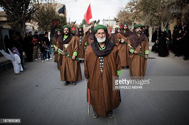 Iranian Muslim Shiite men impersonating the role of soldiers of the army of Prophet Mohammed's grandson Imam Hussein take part in the annual...