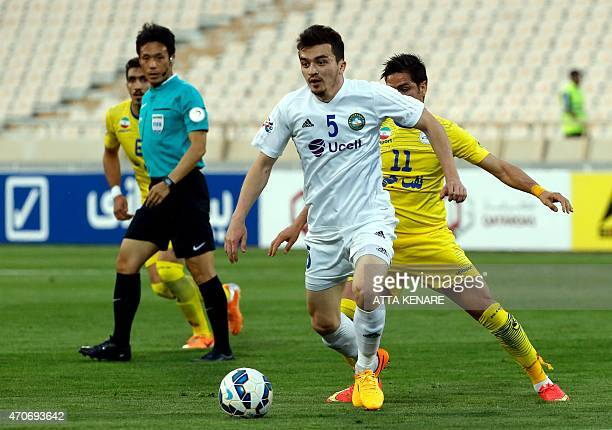 Iranian Naft Tehran's Kamaleddin Kamyabinia fights for the ball with Uzbek Pakhtakor's Akbar Ismatullaev during their AFC Champions League group B...