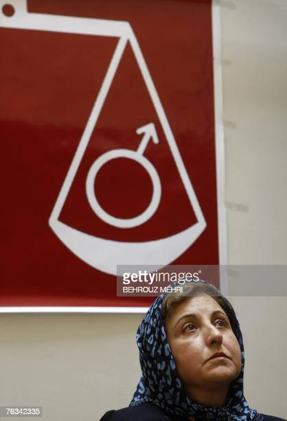 Iranian Nobel peace laureate and women rights activist Shirin Ebadi sits under a scale weighing the male symbol during a press conference in Tehran...