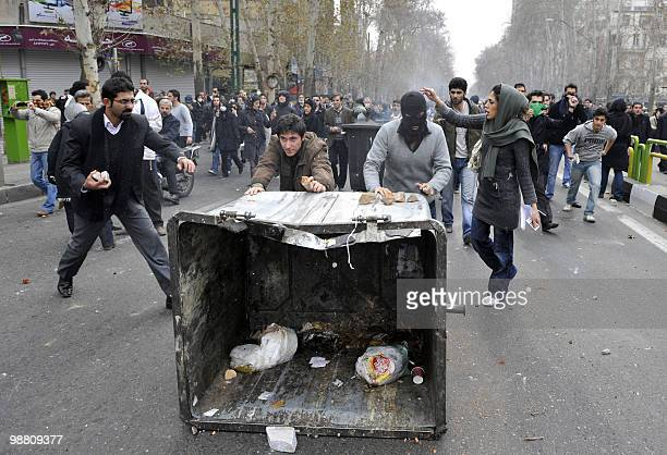 Iranian opposition supporters push a garbage container during clashes with security forces in Tehran on December 27 2009 Four protesters were killed...