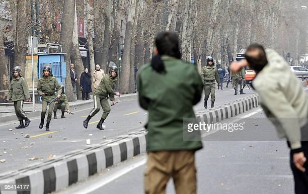 Iranian opposition supporters throw stones towards riot policemen during clashes in Tehran on December 27 2009 At least four protesters were killed...
