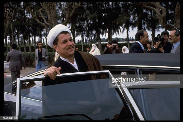 Iranian Parliamentary Pres Hashemi Rafsanjanni stepping into car as he leaves assembly hall during visit to country