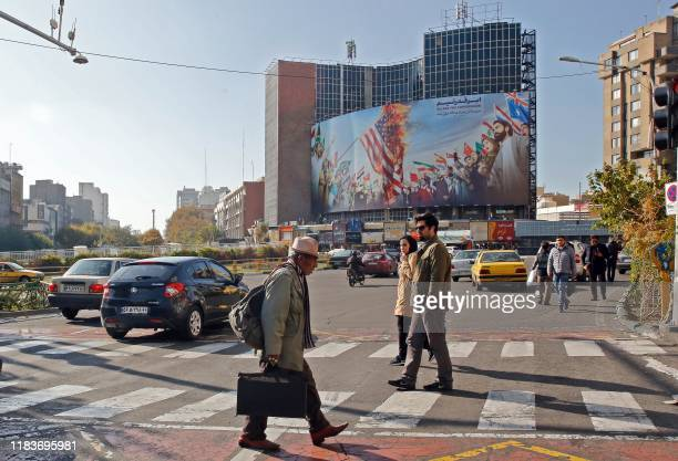 Iranian pedestrians cross a street at Valiasr square in Tehran on November 21 2019