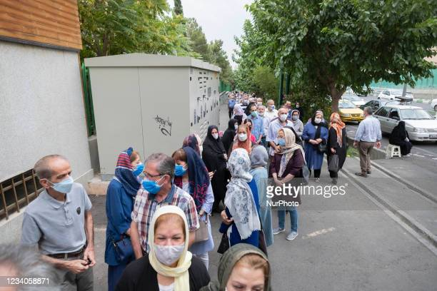 Iranian people wearing protective face masks line-up out of a sport hall while waiting to receive a dose of the China's Sinopharm new coronavirus...