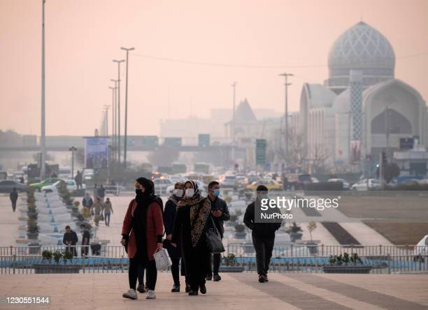 Iranian people wearing protective face masks walk along the Azadi Square in western Tehran during a polluted air, following the COVID-19 outbreak in...