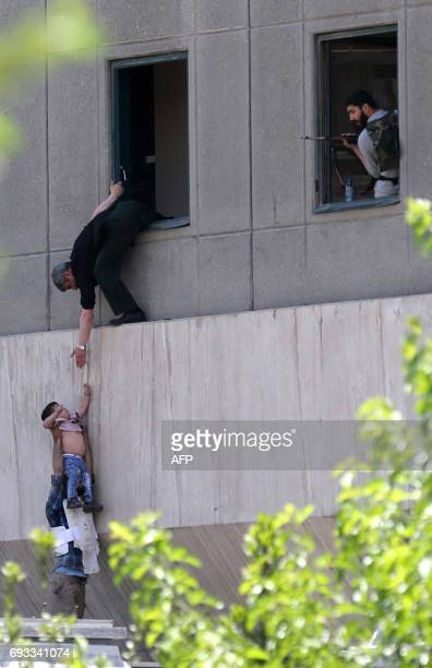 Iranian policemen evacuate a child from the parliament building in Tehran on June 7 2017 during an attack on the complex The Islamic State group...