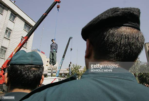 Iranian policemen watch the execution of Hossein Kavousifar and Majid Kavousifar in central Tehran 02 August 2007 Two men convicted of murdering a...