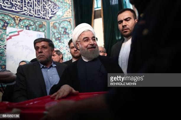 Iranian President and presidential candidate Hassan Rouhani casts his ballot for the presidential elections at a polling station in Tehran on May 19...