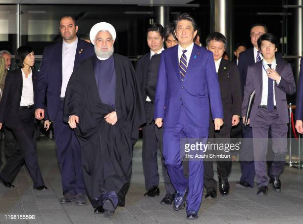 Iranian President Hassan Rouhani and Japanese Prime Minister Shinzo Abe walk to the venue of their dinner at the prime minister's official residence...