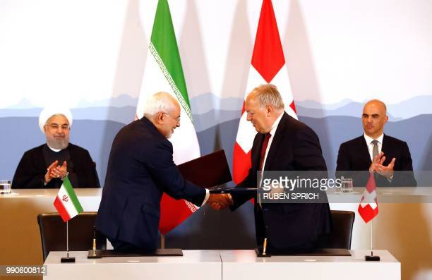 Iranian President Hassan Rouhani and Swiss President Alain Berset clap as Iranian Foreign Minister Mohammad Javad Zarif and Swiss Economic Minister...