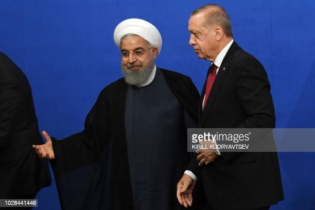 Iranian President Hassan Rouhani and Turkish President Recep Tayyip Erdogan leave after a press conference after a trilateral meeting along with the...