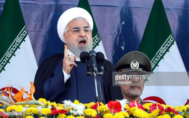 Iranian President Hassan Rouhani delivers a speech during the annual military parade marking the anniversary of the outbreak of the devastating...
