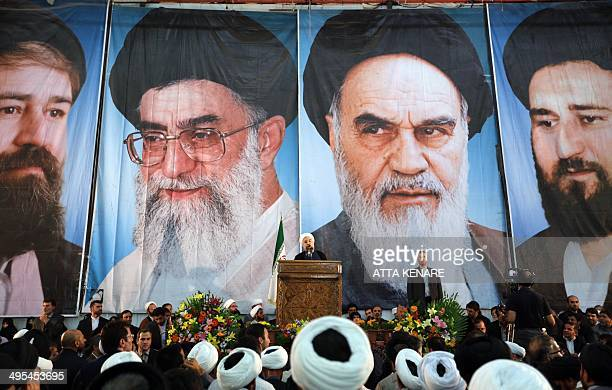 Iranian President Hassan Rouhani delivers a speech under portraits of Iran's supreme leader, Ayatollah Ali Khamenei and Iran's founder of the Islamic...