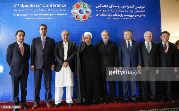 Iranian President Hassan Rouhani gestures as he poses in a group photo with Abdul Rauf Ibrahimi Afghan Parliament Speaker Asad Qaiser Pakistan...